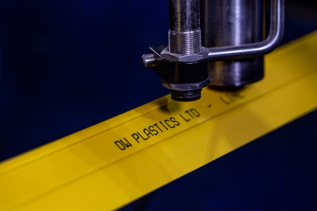Inline printer writing the words DW plastics ltd